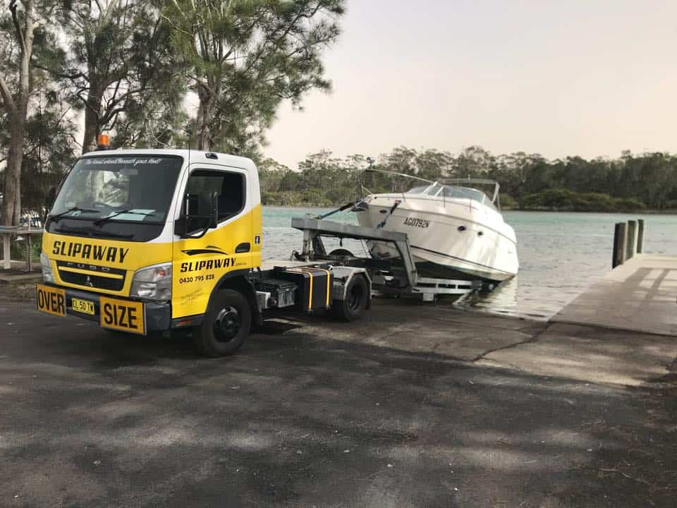 The Slip Away boat transport service picking up a cruiser from a boat ramp