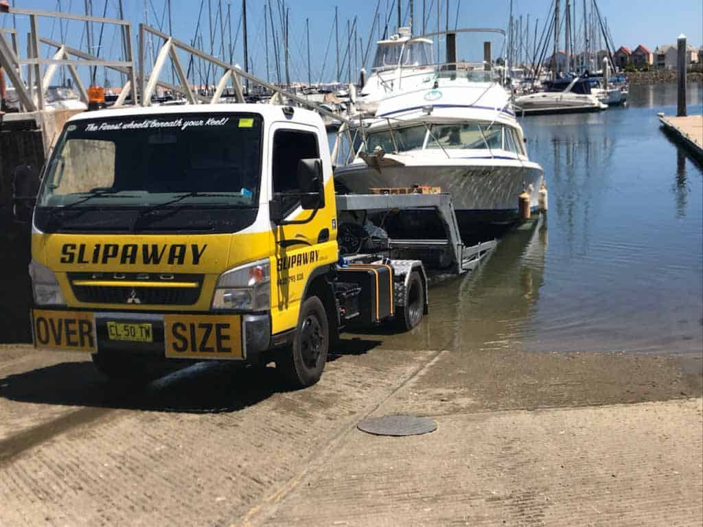 A boat getting ready to be put in the water at boat ramp by Slip Away transportation in Surfers Paradise