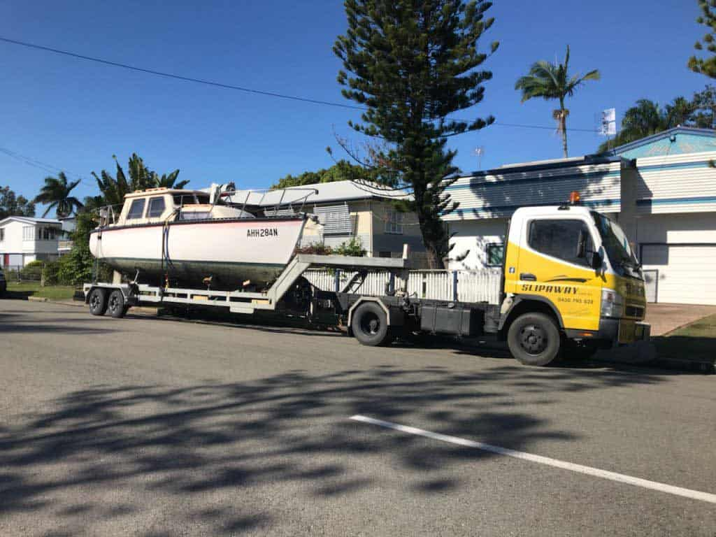 A boat getting ready to be serviced that is picked up from a house by Slip Away transportation