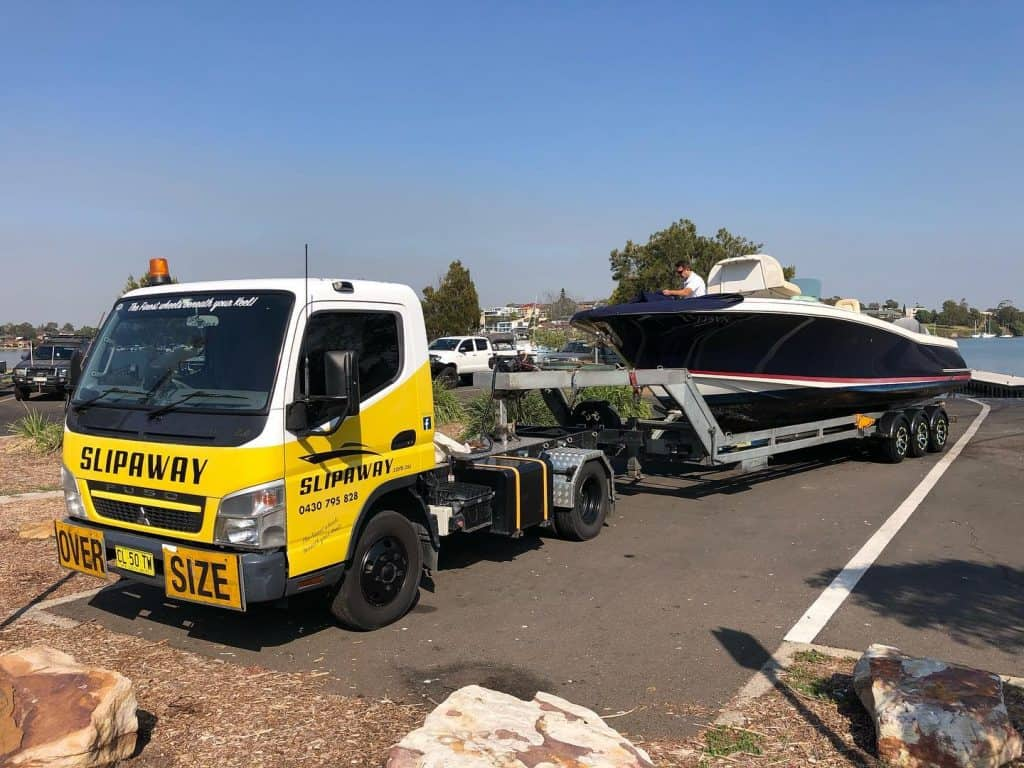A Chris Craft Suntender 29 cruiser boat on its way to Mid Coast Boat Yard for a repaint and T Top conversion being transported by Slip Away Boat Transport service