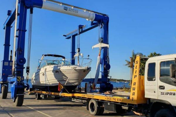 INTERSTATE BOAT TRANSPORT SLIP AWAY MARINE TRANSPORT SERVICE LIFTING A BOAT TO BE MOVED BY ROAD